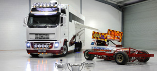 A truck next to a racing car branded with J Davidson